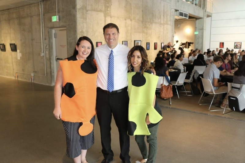 A man smiling with two women dressed up as puzzle pieces