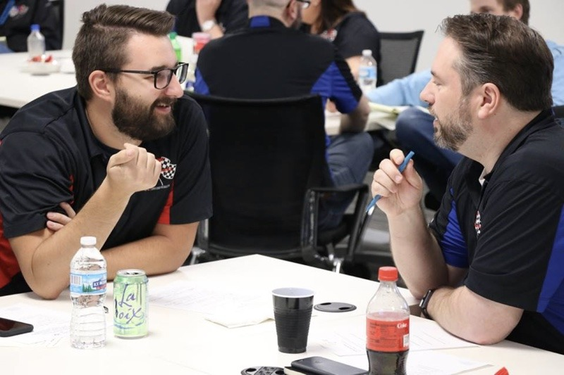 Two men smiling and talking