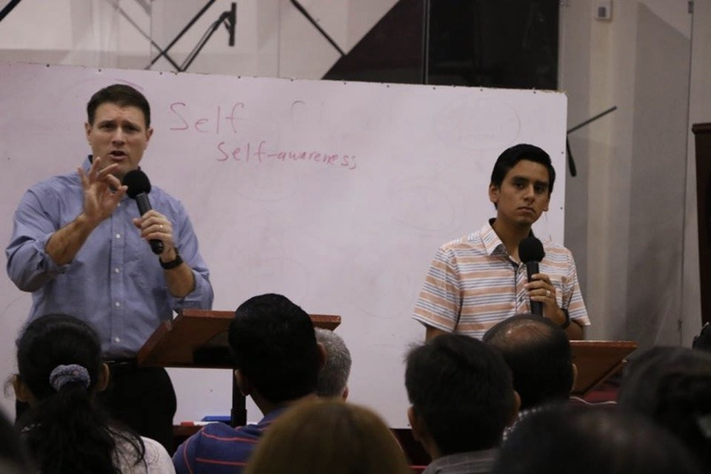 A man speaking while a young man interprets