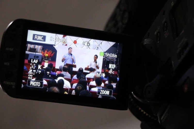Video camera showing man speaking in front of podium